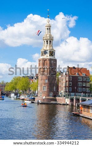 Amsterdam-April 27:  Amsterdam down town with the Montelbaanstoren tower and houseboats along the bank of the canal Oudeschans on April 27,2015 the Netherlands.