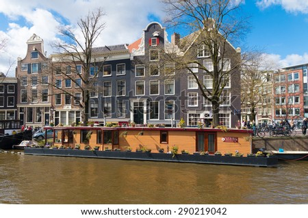 AMSTERDAM - APRIL 4, 2015: Large houseboat in an amsterdam canal. The city counts over 2500 houseboats in his canals - stock photo