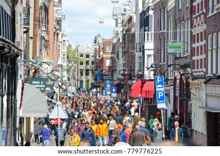 AMSTERDAM-APRIL 27: People on one of the Amsterdam busy street celebrate King's Day on April 27,2015, the Netherlands. Kings Day is the biggest festival celebrating the birth of Dutch royalty.