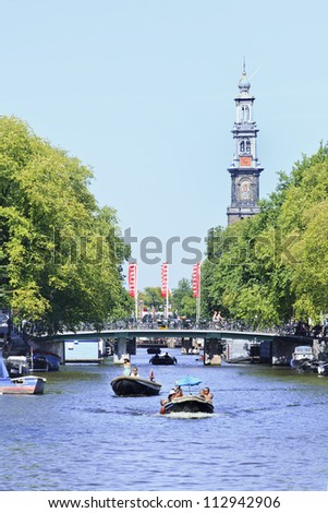 AMSTERDAM-AUG. 18: Canal and Wester Tower on Aug. 18, 2012 inAmsterdam, The Netherlands. It is known as Venice of the North, its beautiful canal belt was finally added to the world heritage list in July 2010. - stock photo