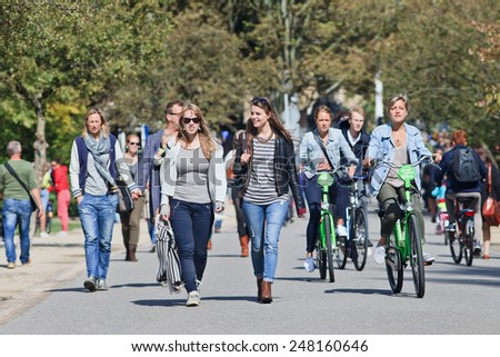 AMSTERDAM-AUG. 24, 2014. Women on foot and by bike have fun in the Vondelpark. The 47 hectares park has annually 10 million visitors, it is named after the 17th century author Joost van den Vondel. - stock photo