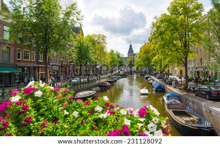 AMSTERDAM - AUGUST 29: Canal in old city at daytime on August 29, 2014 in Amsterdam. - stock photo