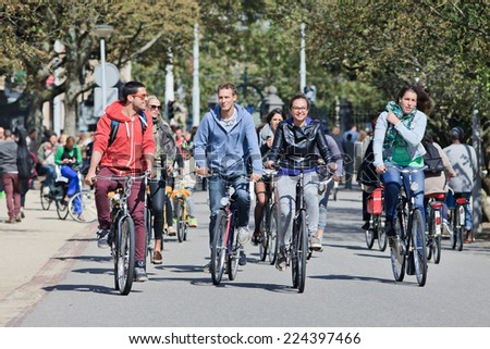 AMSTERDAM-AUGUST 24, 2014. Group of cyclists have fun in Vondelpark. The 47 hectares park has annually around 10 million visitors, it is named after the 17th century author Joost van den Vondel. - stock photo