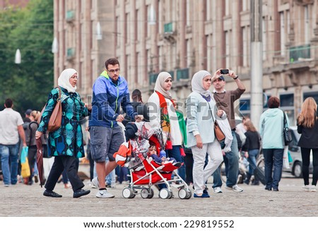 AMSTERDAM-AUGUST 26, 2014. Muslim family walk on the Dam Square. There are an estimated 1.2 million Muslims in the Netherlands, which is equivalent to about 6 percent of the country's population. - stock photo
