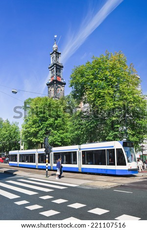 AMSTERDAM-AUGUST 24, 2014. Tram with Wester Tower on background. Transport in the city exist mainly by bicycle and public transport. Amsterdam has 16 different tram lines with total length of 213 KM. - stock photo