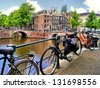 Amsterdam canal scene with bicycles and bridges - stock photo