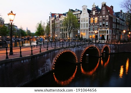 Amsterdam canals lit up at dusk, Netherlands          - stock photo