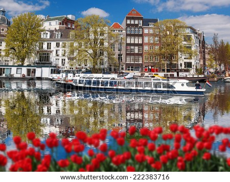Amsterdam city with boats on canal against red tulips in Holland - stock photo