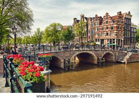 Amsterdam colorful houses, geranium flowers and triple arch bridge at the intersection between Prinsengracht and Brouwersgracht Canals. - stock photo