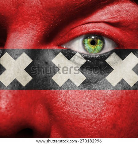 Amsterdam flag painted on a man's face to support his city Amsterdam - stock photo