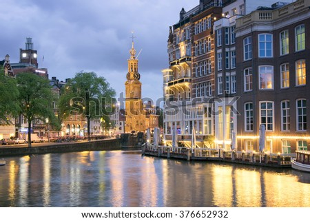 AMSTERDAM, HOLLAND - JUNE 19, 2015: A view of Munttoren at sunset with reflections on the canal