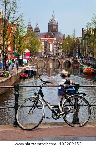 Amsterdam, Holland, Netherlands. Church of St Nicholas, old town canal, boats, bike - stock photo
