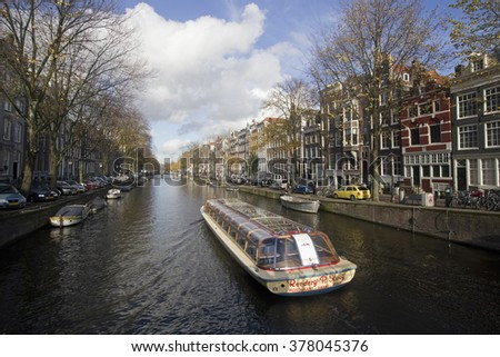 Amsterdam, Holland - November 12, 2015: Amsterdam canal in autumn with large clouds and a tour boat sailing on November 12, 2015 in Amsterdam, Holland. - stock photo