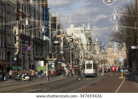 Amsterdam, Holland - November 12, 2015: People waiting at a tramstop in a shopping street decorated for Christmas, with the railway station in the distance, on November 12, 2015 in Amsterdam, Holland. - stock photo