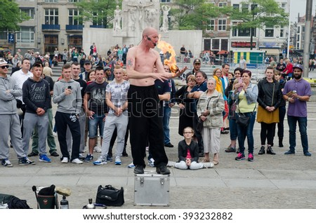 AMSTERDAM, HOLLAND - SEPTEMBER  6, 2014: Street artist playing with fire ball  in Amsterdam - stock photo