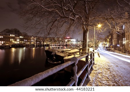 Amsterdam in the Netherlands at night covered with snow - stock photo