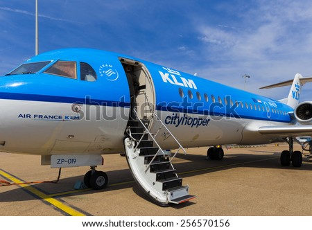AMSTERDAM - 19 JULY, 2014: An Air France KLM Cityhopper Fokker 70 at Schiphol Airport is getting ready for the flight to Toulouse. - stock photo