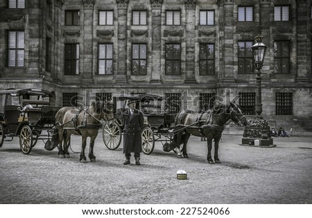 Amsterdam - June 24, 2013 : Old-fashioned carriage with horses and a coachman at the Amsterdam Square, vintage stylized - stock photo