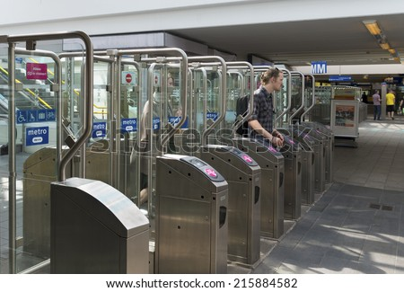 AMSTERDAM - JUNE 7, 2014: Unknown man passing automatic railway station gates for checking in or out
