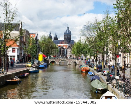 AMSTERDAM - MAY 27, 2011: Oudezijds Voorburgwal street is popular place, because there are many landmarks nearby: church of St.Nicolas or red light street, on May 27, 2011 in Amsterdam.  - stock photo
