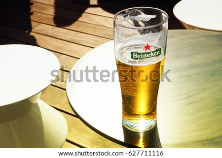 AMSTERDAM, NETHERLANDS - APR 08, 2017 : Glass with Heineken Lager Beer  on outdoor bar table on sunny day. Heineken is the flagship product of Heineken International