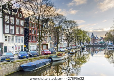 """AMSTERDAM, NETHERLANDS - APRIL 8, 2016: A view towards The Waag (""""weigh house"""") in Nieuwmarkt area of Amsterdam from the Kloveniersburgwal canal in the morning. - stock photo"""
