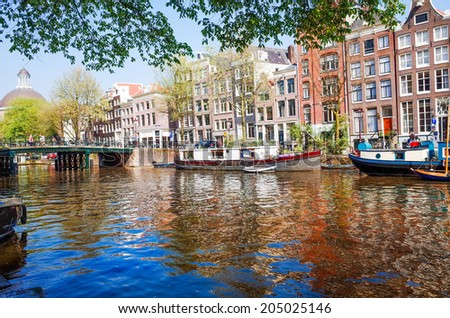Amsterdam, Netherlands.-APRIL 23: Amsterdam canals on April 23, 2014. Beautiful view of Amsterdam canals with bridge and typical dutch houses. - stock photo