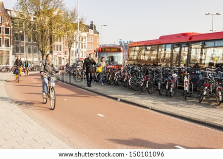 AMSTERDAM, NETHERLANDS - APRIL 22: People go to work by bicycles and buses  on april 22, 2013 in Amsterdam. In Capital of Netherlands are also twice as many bikes then cars. - stock photo