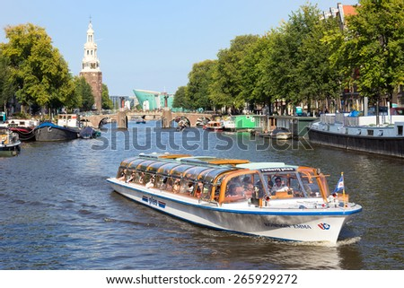 AMSTERDAM, NETHERLANDS - AUG 27, 2014: Canal boat in one of the canals in Amsterdam. The city is the worlds most watery city. It has more than one hundred kilometres of canals. - stock photo