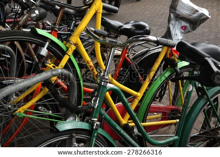 AMSTERDAM, NETHERLANDS - AUGUST 9, 2012: Colourful bicycles parked at the bicycle parking station next to the Central railway station in Amsterdam, Netherlands. - stock photo