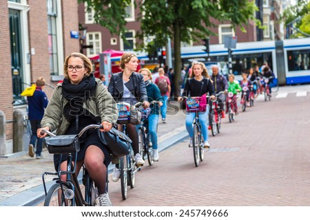 AMSTERDAM, NETHERLANDS - AUGUST 19:  People riding bicycles in historical part in Amsterdam, Netherlands on August 19, 2014 - stock photo