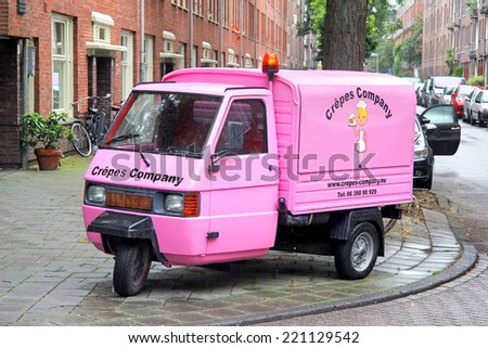 AMSTERDAM, NETHERLANDS - AUGUST 10, 2014: Pink three-wheeled light commercial vehicle Piaggio Ape at the city street. - stock photo
