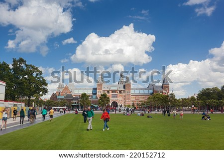 AMSTERDAM - NETHERLANDS: AUGUST 11, 2014: Tourists at Museumplein with Rijksmuseum, one of Amsterdam's grandest museum in background.