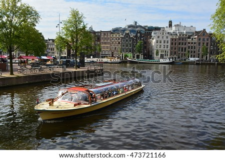 Amsterdam, Netherlands - August 13, 2016: Tourists taking an iconic canal cruise in downtown Amsterdam in 2016 in Amsterdam, Netherlands.