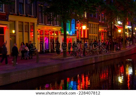 AMSTERDAM, NETHERLANDS - AUGUST 28: Tourists visit Red Light District at night on August 28, 2014 in Amsterdam, Netherlands. In this area there are prostitutes, sex shops and live sex shows - stock photo
