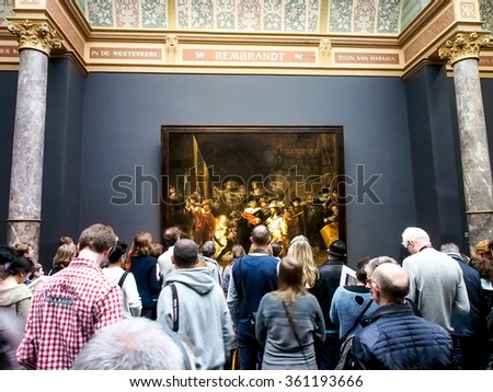 "AMSTERDAM, NETHERLANDS - DEC 27, 2015: Visitors at the famous painting ""Night watch"" at Rijksmuseum, Amsterdam, Netherlands. The Rijksmuseum is dedicated to arts and history in Amsterdam."