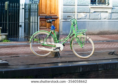 Amsterdam,Netherlands â?? December 23, 2015  : Green bicycle parking on the street near canal on Red Light District in Amsterdam, Netherlands
