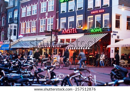 AMSTERDAM, NETHERLANDS - FEB 14, 2014: Unidentified people on the street of an old town of Amsterdam in the dusk.  - stock photo