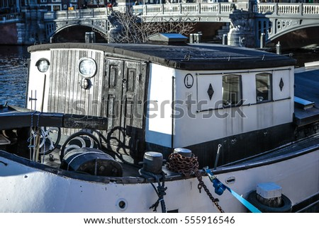 AMSTERDAM, NETHERLANDS - JANUARY 09, 2017: Boats on water in beautiful evening sun set. January 09, 2017 in Amsterdam - Netherland.
