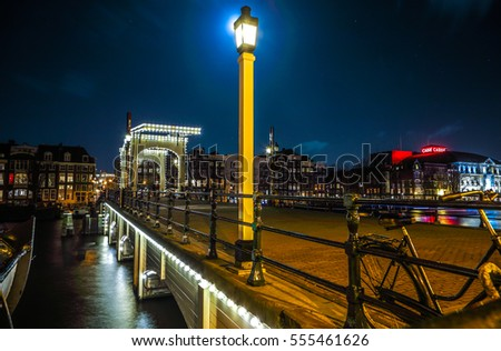 AMSTERDAM, NETHERLANDS - JANUARY 12, 2017: Old wooden Dutch bridge at night time against rush clouds on January 12, 2017 in Amsterdam - Netherlands.