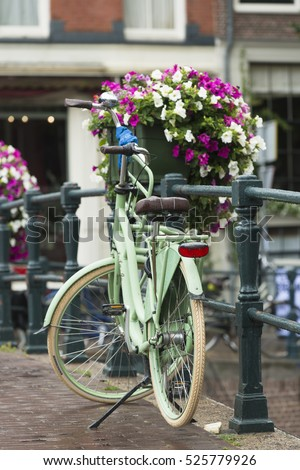 AMSTERDAM, NETHERLANDS - JULY 8, 2015: A bicycle parked at one of the bridges of the city, next to a large pot with flowers.