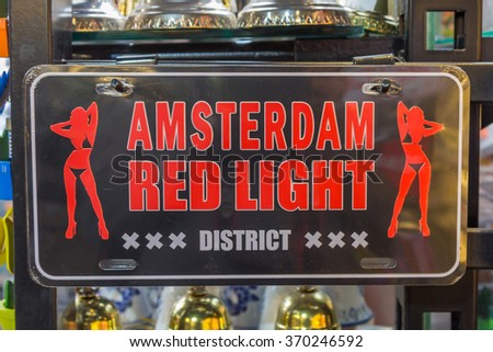 "AMSTERDAM, NETHERLANDS - JULY 29, 2015: A board showing the text ""AMSTERDAM RED LIGHT DISTRICT"". It consists of a network of alleys containing approximately 300 one-room cabins rented by prostitutes."