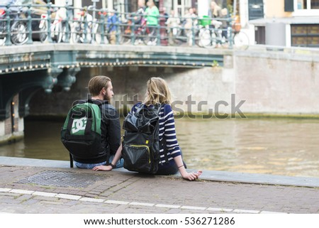 AMSTERDAM, NETHERLANDS - JULY 8, 2015: A couple with backpacks, talking sitting on the edge of one of the canals of the city.