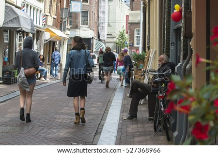AMSTERDAM, NETHERLANDS - JULY 8, 2015: An elderly bearded man sitting in a doorway, sees two attractive young women passing in front of him.