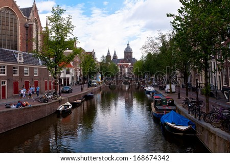 AMSTERDAM, NETHERLANDS - JULY 28, 2013: Common view of houses and canals of Amsterdam in summer of 2013.