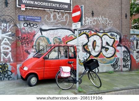 AMSTERDAM, NETHERLANDS - JULY 27, 2014: Small car and bike on the background of graffiti, Amsterdam, Holland - stock photo