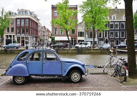 AMSTERDAM, NETHERLANDS -10 JUNE 2015- A vintage Citroen 2CV car is parked on the street along a canal in Amsterdam. The iconic Deux Chevaux was produced by Fiat between 1948 and 1990. - stock photo