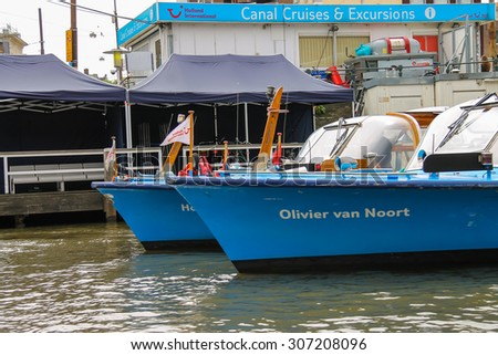 Amsterdam, Netherlands - June 20, 2015: Excursion ships are near the pier on the waterfront in Amsterdam - stock photo