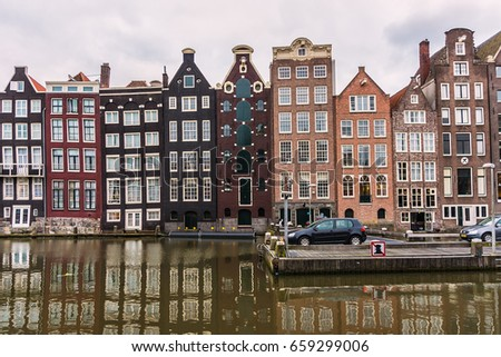 AMSTERDAM, NETHERLANDS - JUNE 17, 2014: Houses at the waterside of the Damrak at sunset.