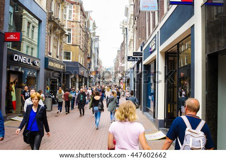 Amsterdam, Netherlands - June 12, 2016: People wandering around Kalverstraat on a cloudy day. The Kalverstraat is a busy shopping street which begins at Dam Square and ends roughly 750 meters down.